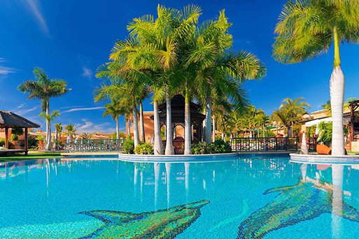 A luxurious and sunny resort pool, palm trees and scattered sheltered sun bed huts. The pool depicts dolphins created using coloured mosaic tiles forming the foundations of the pool