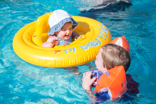 A baby and a toddler swimming in a pool