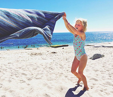 Young girl in swimming costume shaking a towl on the beach