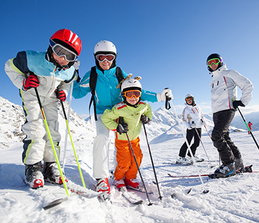 A young family posing for a picture whilst in full ski equipment