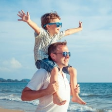Young boy with sunglasses sat on dads shoulders on the beach