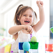 Toddler laughing and playing with water paint