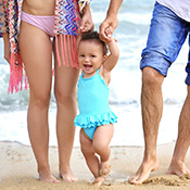 Young toddler being walked on the beach with mum and dad