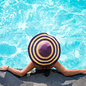 Lady relaxing in a pool wearing a sunhat photographed from above