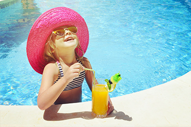 Young girl sipping orange cocktail in a pool with a pink hat and swimming costume