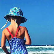 Young girl on the beach with swimming costume and turquoise sun hat