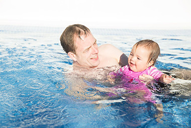 dad in the pool teaching a toddler to swim