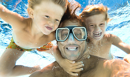 dad underwater with goggles and two sons holding on to him to pose for a photograph