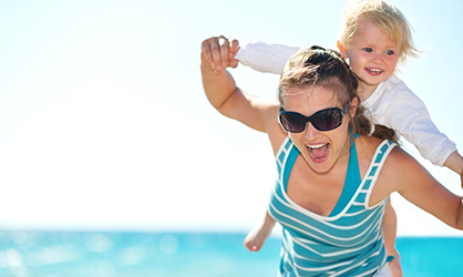 mum running on a beach with toddler on her shoulders